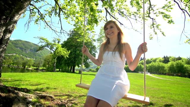 stockvideo's en b-roll-footage met girl in white dress swinging on rope swing under tree - witte jurk