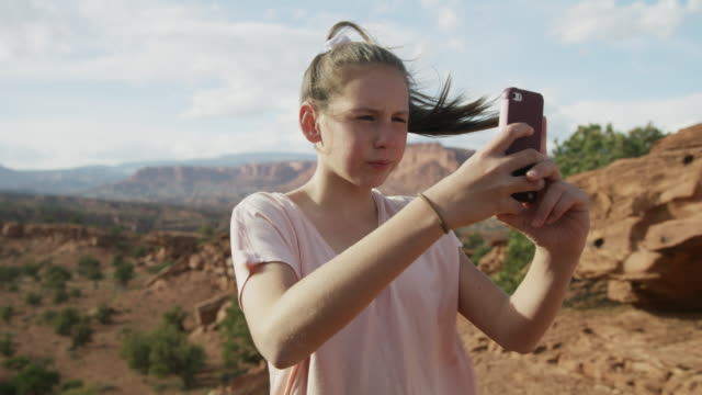 girl in windy desert photographing scenic view by panning cell phone / capitol reef national park, utah, united states - pferdeschwanz stock-videos und b-roll-filmmaterial