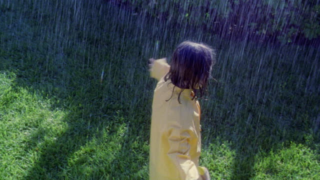 OVERHEAD girl in yellow raincoat holding yellow umbrella spinning around sticking out tongue in rain