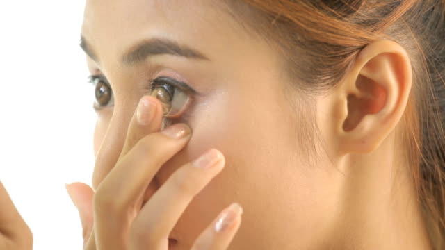 Girl inserting contact lens in her eye