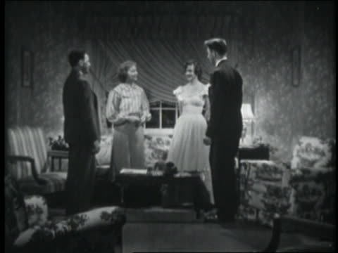 B/W 1948 girl introducing date to her parents in living room / they sit + chat