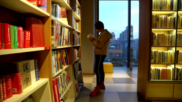girl is choosing books in the bookstore - bookshelf stock videos & royalty-free footage