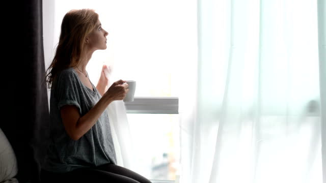 Girl is drinking her coffee and watching through window