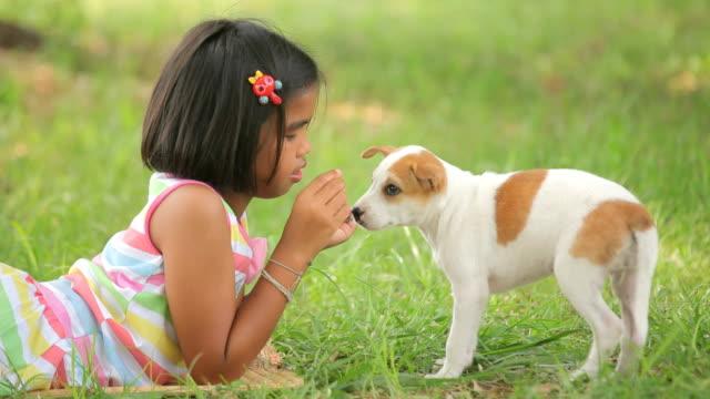 girl is feeding her puppy dog