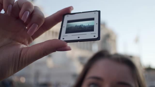 女の子は写真を見て、写真映画を保持しています - ラツィオ州点の映像素材/bロール