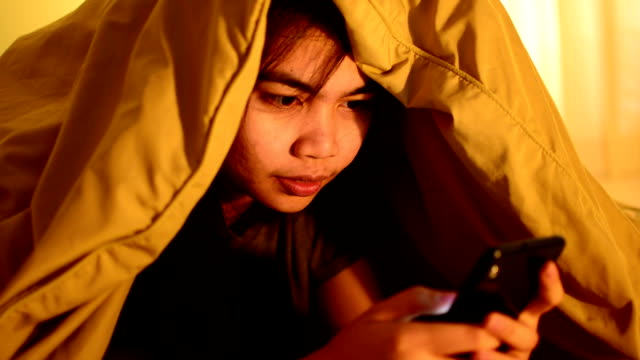 girl is playing game on the phone under the covers. - duvet stock videos & royalty-free footage