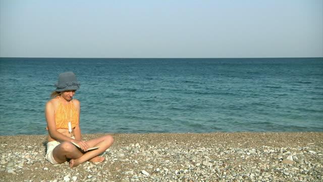 vídeos de stock e filmes b-roll de menina é ler na praia - só meninas adolescentes