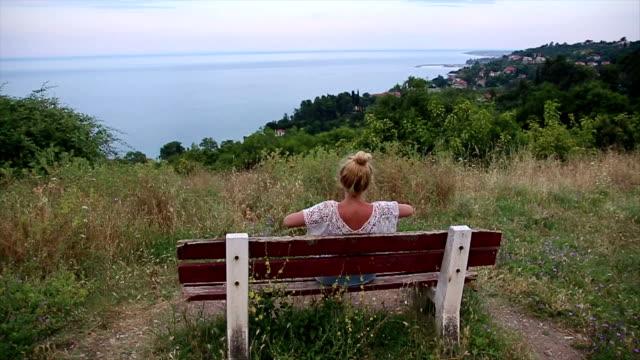 vídeos y material grabado en eventos de stock de chica está sentado en el banco cerca del mar - espalda humana