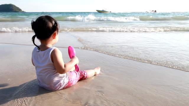 Girl is sitting and see the sea with her toy