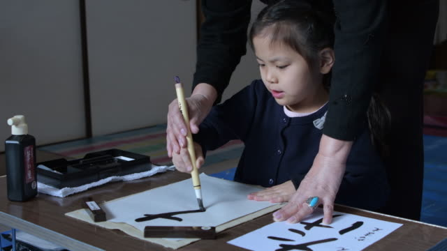 vidéos et rushes de girl japanese calligraphy taught by a teacher. - art et artisanat