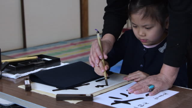 girl japanese calligraphy taught by a teacher. - kunst und kunsthandwerk stock-videos und b-roll-filmmaterial