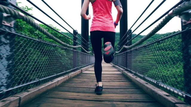 vídeos de stock e filmes b-roll de mulher corrida na ponte - ponte suspensa
