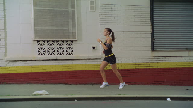 ms pov girl jogging with ipod and earphone on pathway /new york, new york, united states - stereo personale video stock e b–roll
