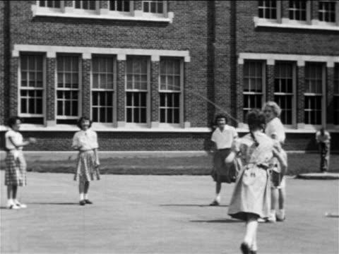 vídeos y material grabado en eventos de stock de b/w 1950 girl joining jump roping girls on playground near school / educational - cuerda de saltar