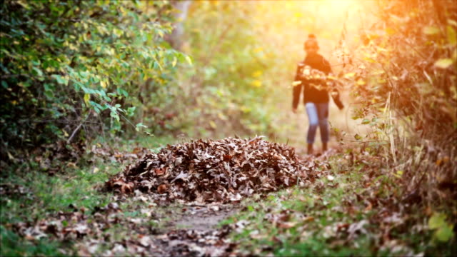 girl jumping into pile of leaves