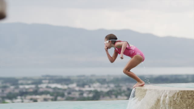 slo mo ws girl (6-7) jumping into swimming pool / cedar hills, utah, usa - one girl only stock videos & royalty-free footage