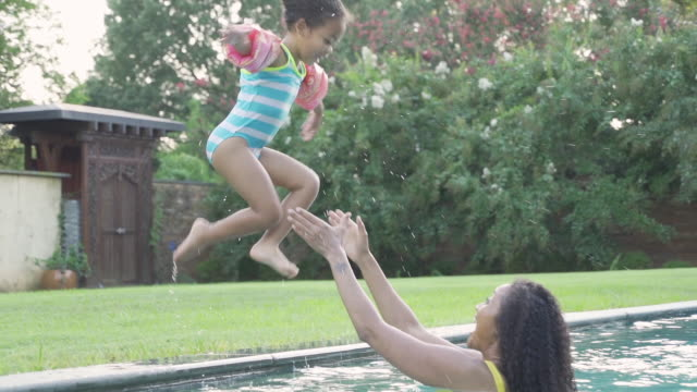 girl jumping into swimming pool - afrikanischer abstammung stock-videos und b-roll-filmmaterial