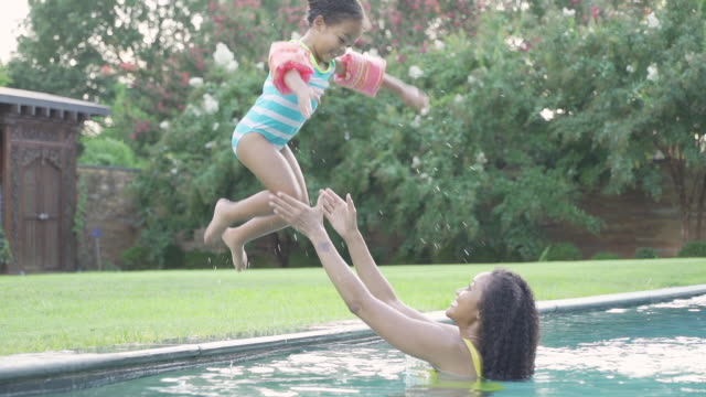 vídeos y material grabado en eventos de stock de girl jumping into swimming pool - familia con un hijo