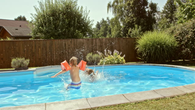slo mo cs a girl jumping into the pool with her younger brother - lawn stock videos & royalty-free footage