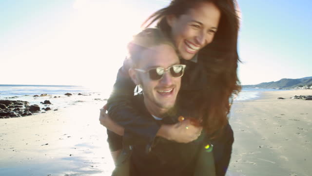 ms girl jumping on boyfriends back at beach / malibu, california, united states - drehen stock-videos und b-roll-filmmaterial