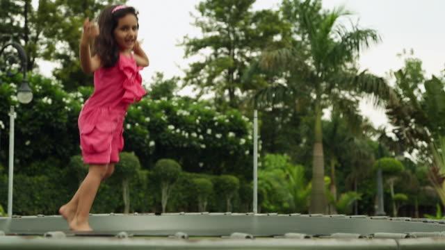 girl jumping on the trampoline, delhi, india - pedana elastica per saltare video stock e b–roll