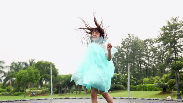 vídeos de stock e filmes b-roll de girl jumping on the trampoline - trampolim equipamento desportivo