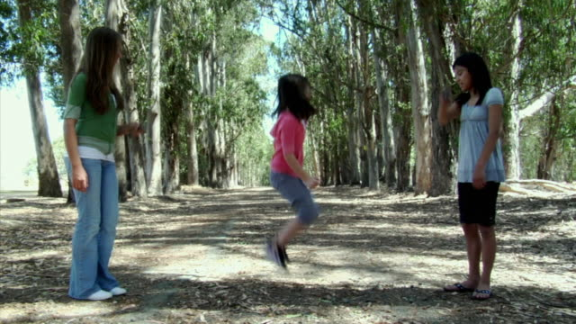 MS, Girl (6-7) jumping rope held by two people on dirt track in eucalyptus forest, Richmond, California, USA