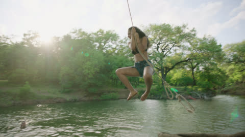 ws slo mo. girl jumps from riverbank with rope swing and splashes into the water with friends. - freedom stock-videos und b-roll-filmmaterial
