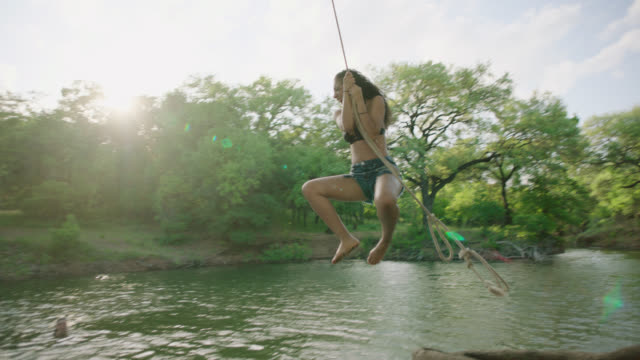 ws slo mo. girl jumps from riverbank with rope swing and splashes into the water with friends. - 揺れる点の映像素材/bロール