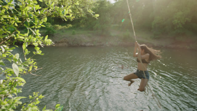 ws slo mo. girl jumps from riverbank with rope swing and splashes into water as friend claps and cheers. - rope swing stock videos & royalty-free footage