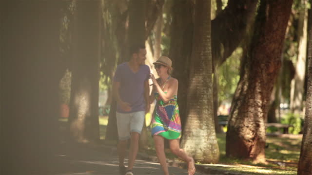 girl jumps on boyfriend's back as they run through sunny rio park - サンドレス点の映像素材/bロール