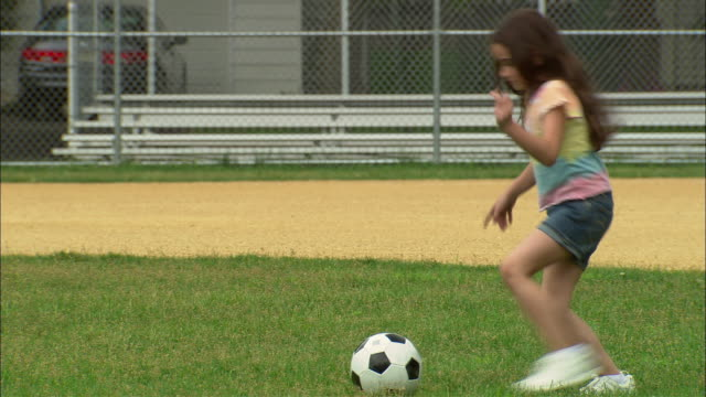 ws girl kicking soccer ball and dancing on baseball diamond/ fanwood, new jersey - one girl only stock videos and b-roll footage