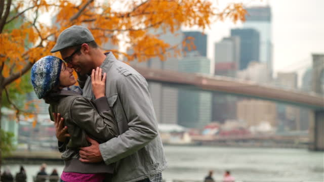 girl kisses boyfriend's forehead as they embrace in autumn park with brooklyn bridge and new york skyline in background (dolly-shot) - forehead stock videos and b-roll footage
