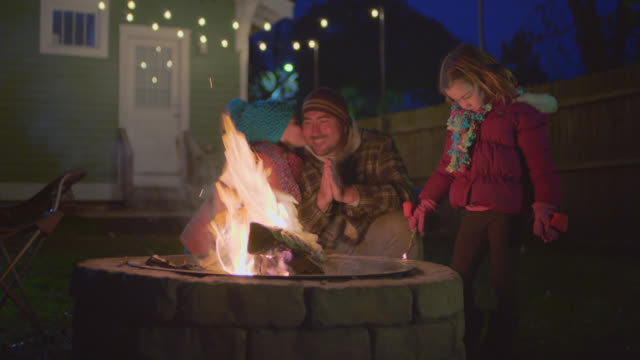 WS. Girl kisses dad on cheek while warming hands around backyard fire pit under Christmas lights.