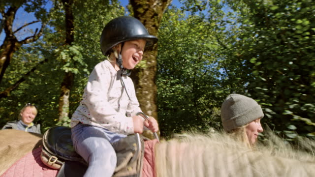 girl laughing while riding on a horse in sunshine - horseback riding stock videos & royalty-free footage