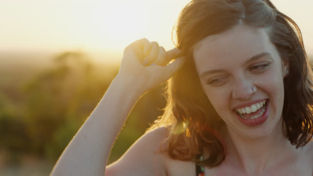 CU SLO MO. Girl laughs out loud with lens flare as sun sets on green mountainside.