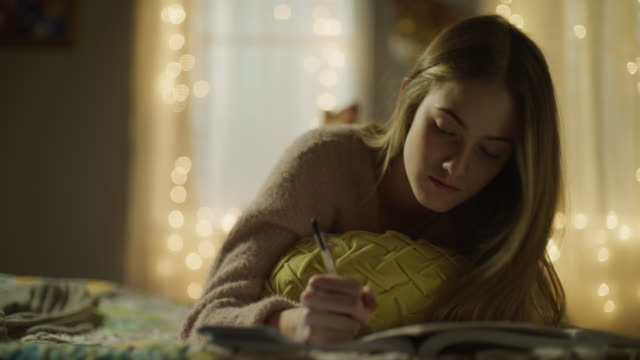 girl laying on bed at night using cell phone as calculator while doing homework / cedar hills, utah, united states - rechenmaschine stock-videos und b-roll-filmmaterial