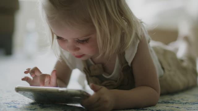 girl laying on floor scrolling on cell phone / american fork, utah, united states - bildschärfe stock-videos und b-roll-filmmaterial