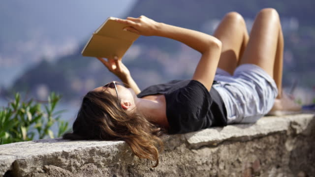 girl laying on her back on stone wall reading a book - top capo di vestiario video stock e b–roll