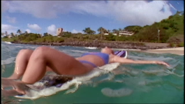 girl laying on surf board in california - one young woman only stock videos & royalty-free footage