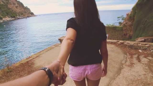 vidéos et rushes de girl leading the way walking with his boyfriend holding hands over a abandoned building in the mediterranean sea costa brava of girona recorded from personal perspective. follow me. - suivre activité avec mouvement