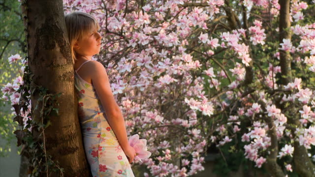 MS Girl (8-9) leaning against tree, smelling magnolia flower, Vrhnika, Slovenia