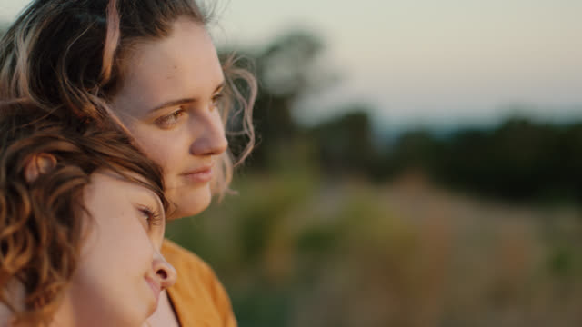 MS SLO MO. Girl leans on sister and looks out at mountain sunset.