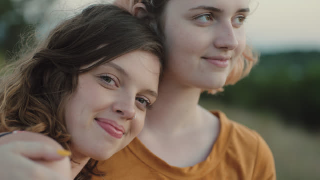 ms slo mo. girl leans on sister and smiles at camera on windy hillside. - umarmen stock-videos und b-roll-filmmaterial