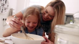 Girl learning baking with her mother.
