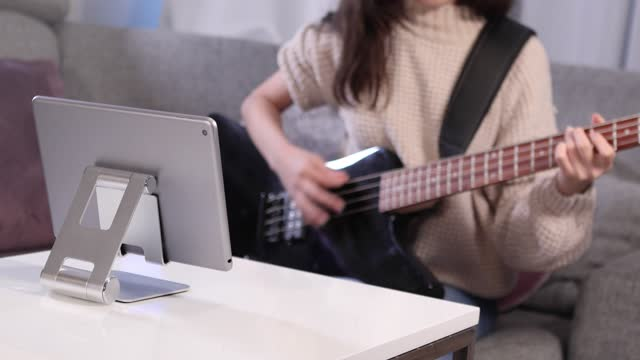 girl learning to play electric bass guitar online - bass guitar stock videos & royalty-free footage