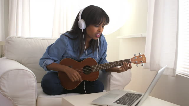 vídeos de stock e filmes b-roll de girl learning to play ukulele with laptop computer - cabelo preto