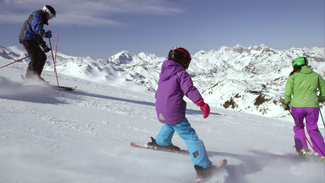 ts girl learning to ski on sunny day with parents - ski slope stock videos & royalty-free footage