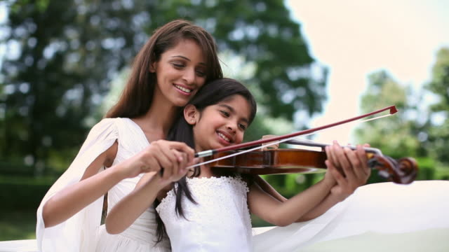 Girl learning violin with the help of her teacher