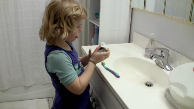 vidéos et rushes de ms girl (6-7) licking toothpaste / brooklyn, new york, usa - presser